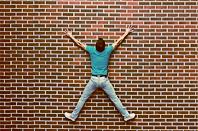Murované domy - Nie je tehla ako tehla. Človek prilepený na tehlovú stenu.